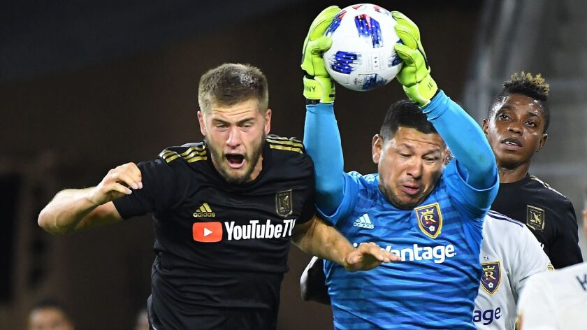 "LAFC's Walker Zimmerman tries to head the ball into the net, but Real Salt Lake goalie Nick Rimando makes a save during the team's playoff game last season. Zimmerman said that season-ending loss left ""a bitter taste in our mouth."""