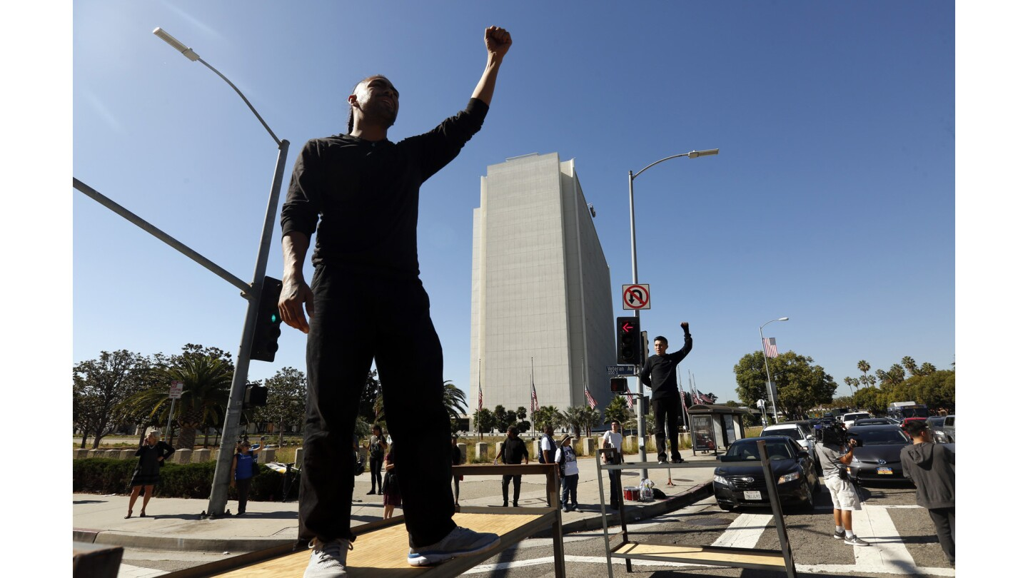Immigrant rights activists, some standing on bunk-bed frames, block traffic in Westwood as part of demonstrations coinciding with the Oct. 5 deadline for Deferred Action for Childhood Arrivals recipients to renew their permits.