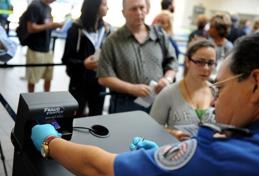 A TSA agent checks an identification card at LAX. In the wake of Friday's fatal shooting of a TSA screener at the airport, specialists on hate crimes and union officials decried what they say is a general atmosphere of mockery and derision toward TSA agents.