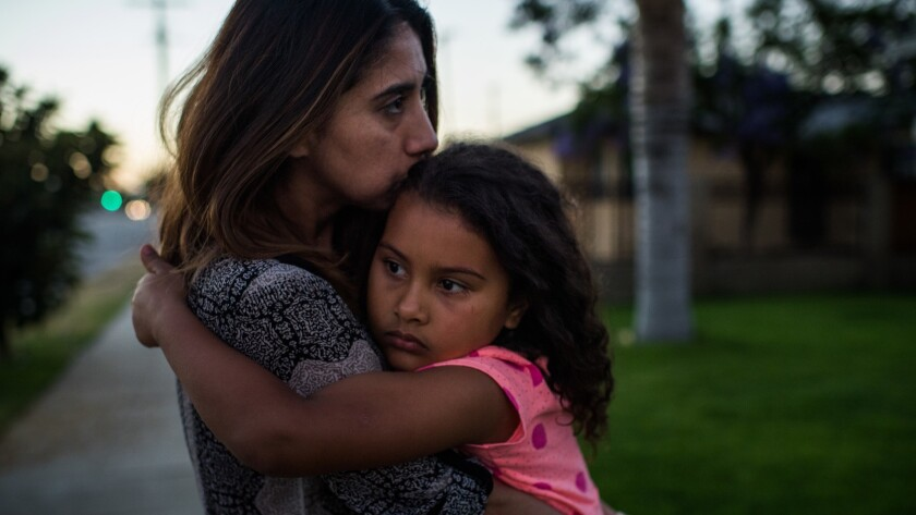 More than a week after the arrest of her father, Jose Luis Garcia, as he watered his lawn, Natalie Garcia tries to console her daughter Marley outside their home in Arleta.