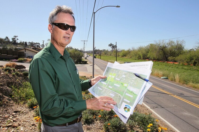 San Marcos Director of Public Works Mike Edwards stands along Discovery Street across from the now nearly dry San Marcos Creek. In his hands are plans for $62 million in coming upgrades, including two bridges, a levee and wider roads.