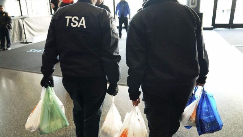 TSA workers leave an event for furloughed federal employees put on the by the Food Bank For NYC in New York on Jan. 22, 2019.