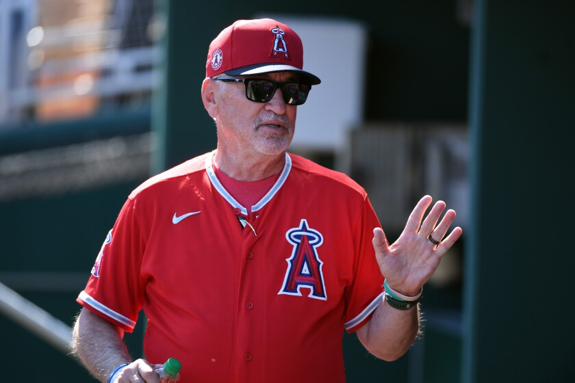 Angels manager Joe Maddon speaks with players in the dugout.