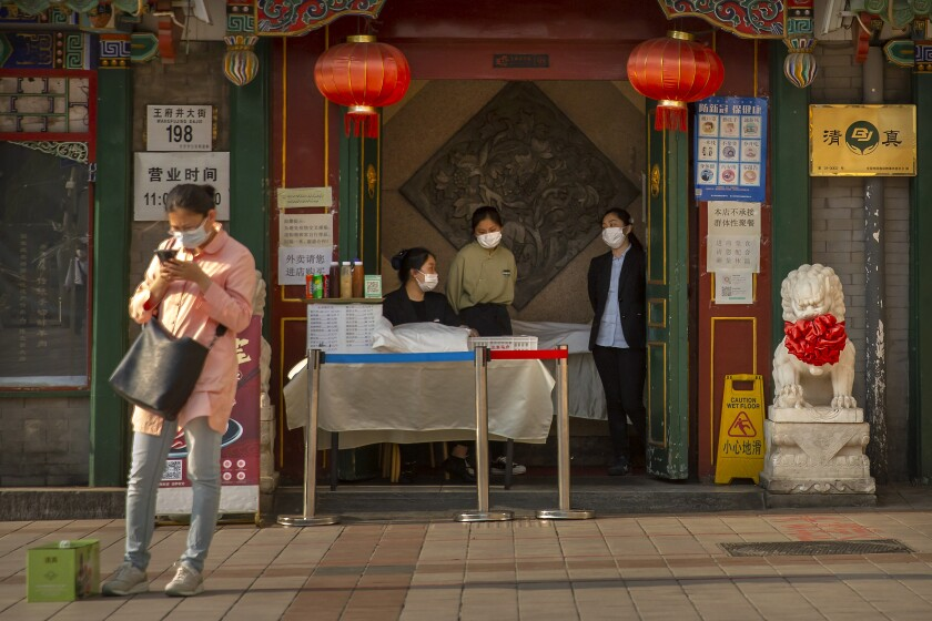 Clerks wear masks to prevent the spread of the coronavirus as they wait for customers at a restaurant in Beijing.