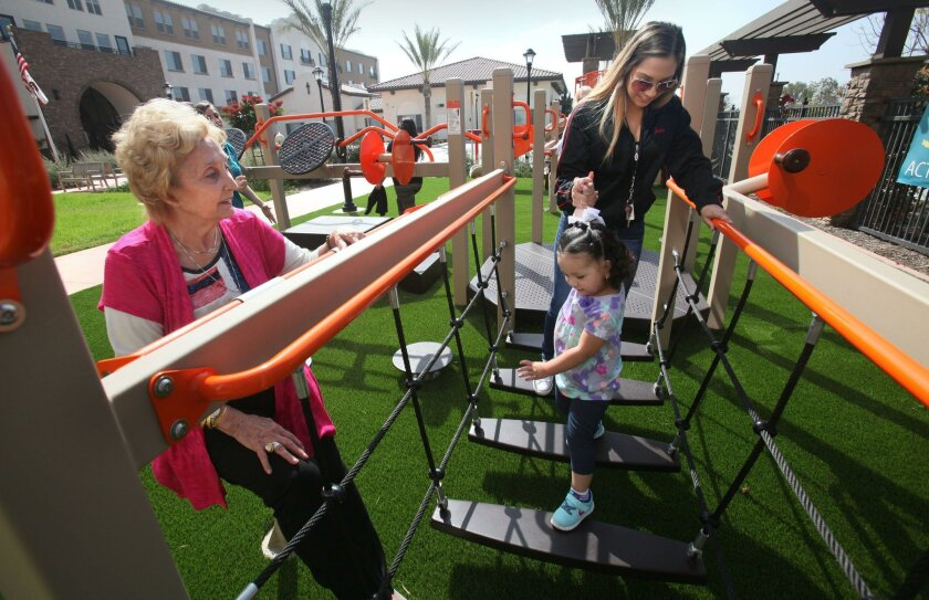 Jean Naddour, 91, left, works on an arm strengthening exercise as Jesenia Lopez walks her niece Alexandra Gomez, 2, on a horizontal ladder.