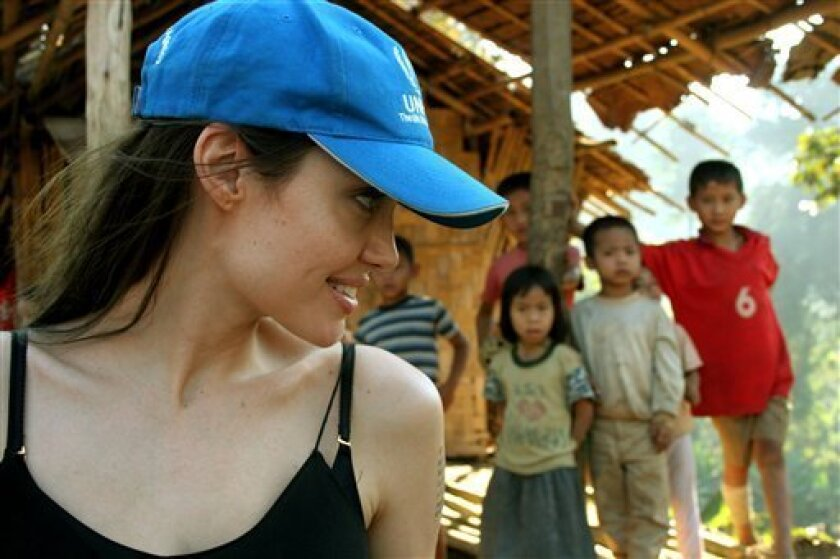 In this image made available in London by the United Nations High Commision for Refugees, Friday, Feb. 6, 2009, UNHCR Goodwill Ambassador Angelina Jolie smiles with Karenni refugee children in the Ban Mai Nai Soi refugee camp in northern Thailand, during a one-day visit on Wednesday, Feb. 4, 2009. (AP Photo/ UNHCR/K.McKinsey)