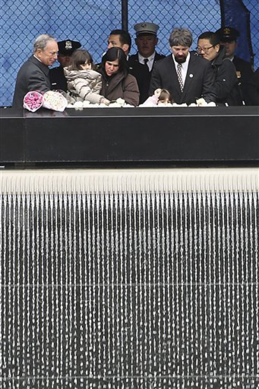 """New York City Mayor Michael Bloomberg, left, joins Stephen Knapp Jr., right, and his family as they lay flowers during a ceremony to honor the six people who died 20 years ago in the first terrorist attack on the World Trade Center, Tuesday, Feb. 26, 2013 in New York. Knapp's father, Stephen Knapp, was killed in the bombing. About 50 people attended the ceremony, held at the 9/11 memorial, where the twin towers were destroyed eight years later. The moment of silence was observed at 12:18 p.m., the time when a truck bomb was detonated below the north tower. The victims' names were read by family members before bagpipers played """"Amazing Grace."""" (AP Photo/Mary Altaffer)"""