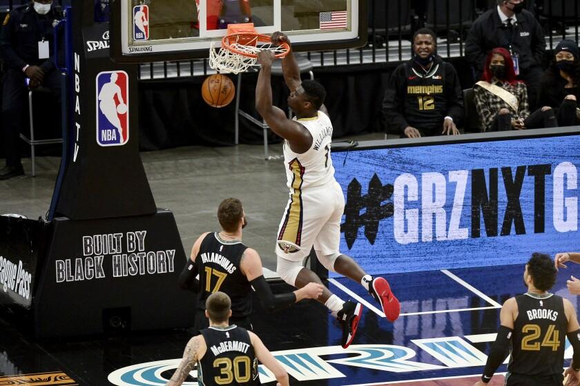 New Orleans Pelicans forward Zion Williamson (1) dunks next to Memphis Grizzlies center Jonas Valanciunas (17) during the first half of an NBA basketball game Tuesday, Feb. 16, 2021, in Memphis, Tenn. (AP Photo/Brandon Dill)
