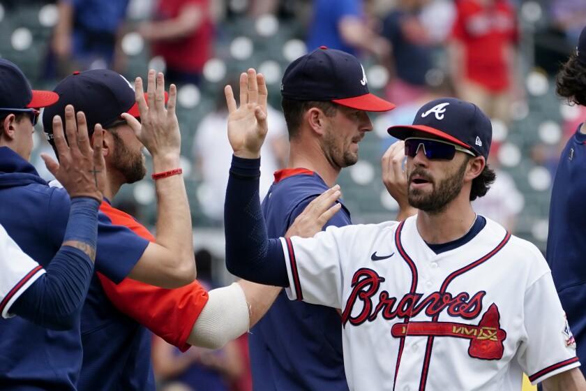 Atlanta Braves' Dansby Swanson (7) high fives his teammates after defeating the Washington Nationals 5-1 in a baseball game Thursday, June 3, 2021, in Atlanta. (AP Photo/John Bazemore)