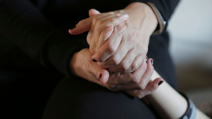 Kira Stanley, 15, at her Encinitas home Friday holding hands with her mother, Wendy Stanley. photo b