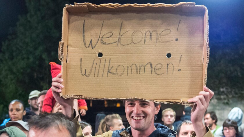 In this Sept. 5, 2015, picture, a man holds a sign welcoming arriving refugees at the train station in Saalfeld, central Germany.