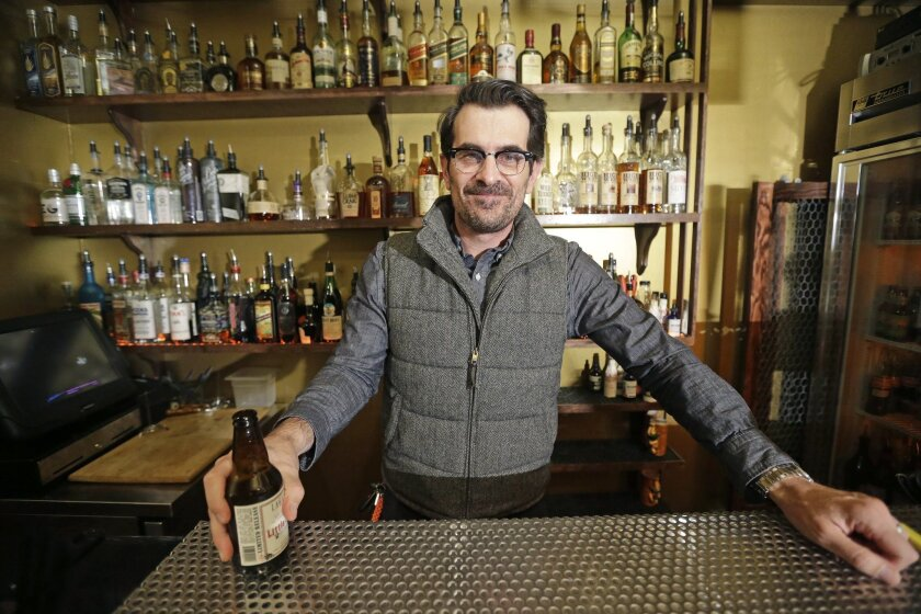 "In this April 16, 2014 photo, actor Ty Burrell, who plays bumbling dad Phil Dunphy on ABC's ""Modern Family,"" poses holding a beer at Bar X, the cocktail bar he co-owns, in Salt Lake City. Burrell just opened Beer Bar, a beer garden-like eatery next door to Bar X that serves 150 beers paired up with"