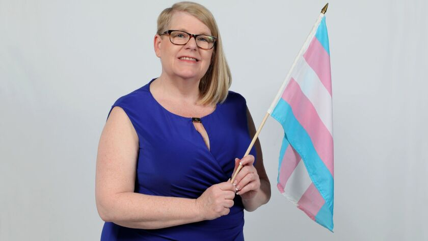 Kathie Moehlig, founder and executive director of TransFamily Support Services, with the transgender flag.