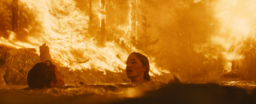 With flames all around, Finn Little's and Angelina Jolie's characters are submerged up to their necks in a lake.