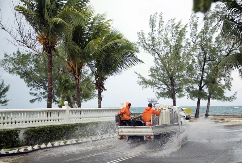 Gente va en un camión por calles parcialmente inundadas por lluvias previas al arribo del huracán Matthew a Nassau, Bahamas, miércoles 5 de octubre de 2016. (AP Foto/Craig Lenihan)