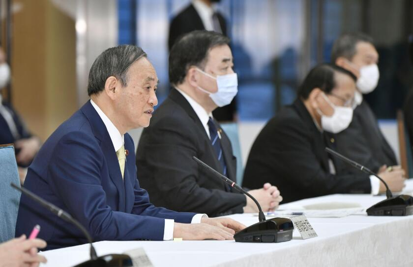 Japanese Prime Minister Yoshihide Suga, left, at a Cabinet meeting