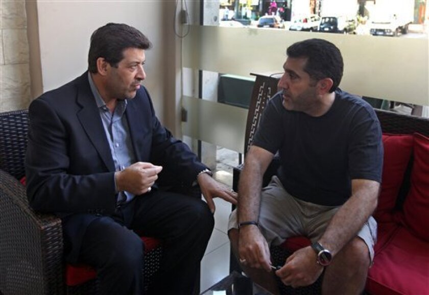 In this Wednesday, July 10, 2013 photo, Shiites Hassan Alayan, left, who was expelled from the UAE in 2009, speaks with Ali Rashid, right, who was expelled from the UAE in 2011, at a cafe in Beirut, Lebanon. Long considered by authorities as a security threat, hundreds of Shiites have been quietly