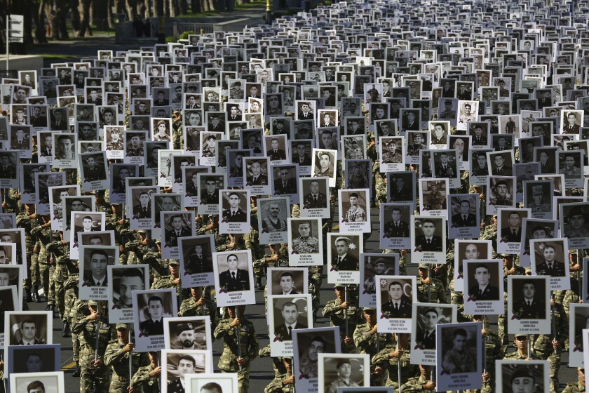 Azerbaijan's Army soldiers carry portraits of the soldiers killed during the fighting over Nagorno-Karabakh in 2020 year, during a memorial event in Baku, Azerbaijan, Monday, Sept. 27, 2021. Azerbaijan and Armenia are marking the first anniversary of the start of their six-week war in which more than 6,600 people died and that ended with Azerbaijan regaining control of large swaths of territory. Soldiers carrying photos of comrades killed in the war marched Monday through the center of the Azerbaijaini capital Baku. (AP Photo/Aziz Karimov)