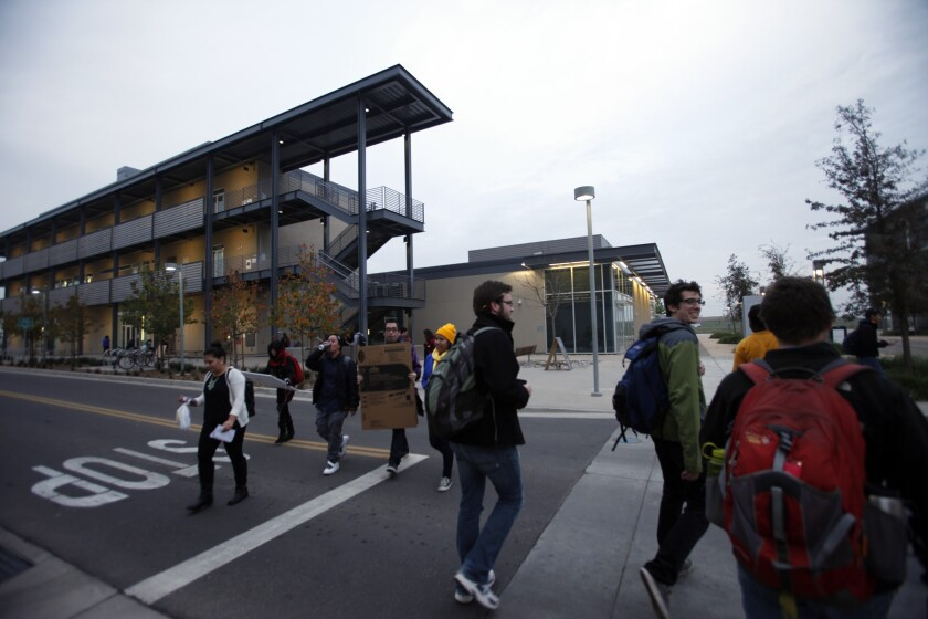 Students make their way toward the Student Services Building on the UC Merced campus in December 2014.