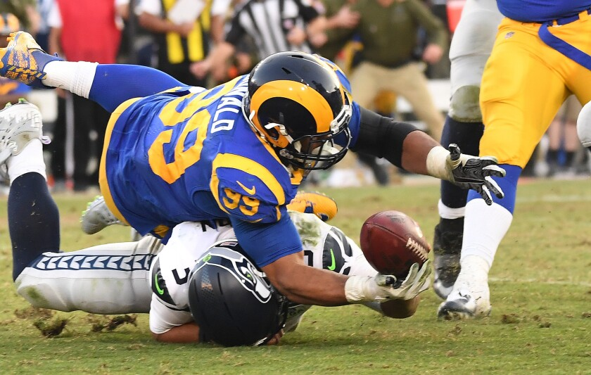 Rams' Aaron Donald falls on Seattle Seahawks quarterback Russell Wilson while trying to recover a fumble in the fourth quarter at the Coliseum on Sunday.