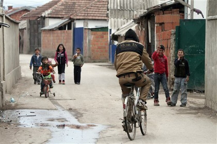 Kosovo Roma drives his bicycle in Kosovo Polje on Friday , April 8, 2011. Kosovo Roma say the International Roma Day is a day to celebrate Roma culture and raise awareness of the issues facing Roma people. (AP Photo/Visar Kryeziu)