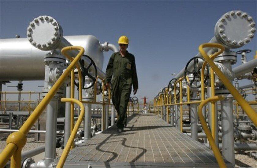 In this April 15, 2008 file photo Iranian oil technician Majid Afshari makes his way to the oil separator facilities in Iran's Azadegan oil field southwest of Tehran, Iran.