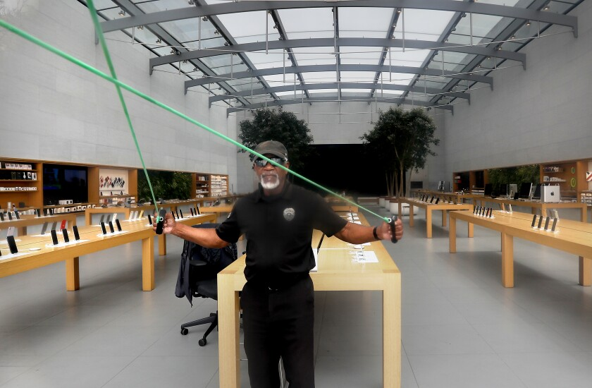 A security guard gets some exercise while keeping watch on the Apple Store on the Third Street Promenade in Santa Monica on May 8.