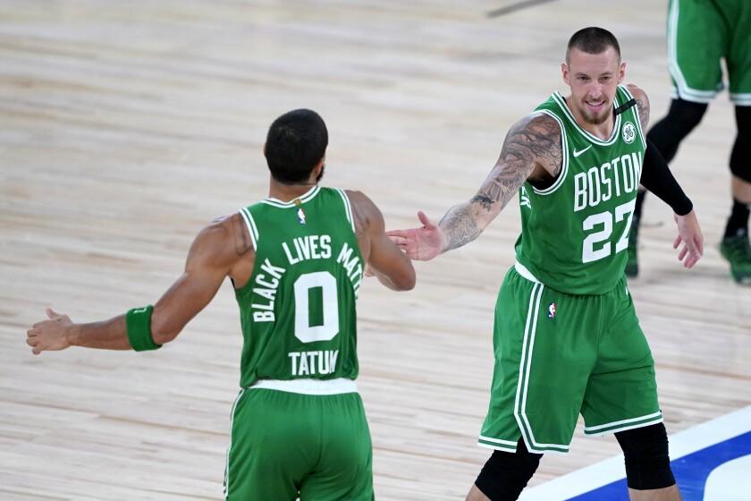 Boston Celtics' Jayson Tatum (0) celebrates his three-pointer with Daniel Theis (27) during the second half of an NBA basketball game against the Toronto Raptors Friday, Aug. 7, 2020 in Lake Buena Vista, Fla. (AP Photo/Ashley Landis, Pool)
