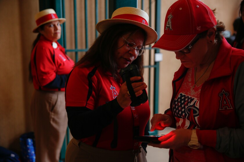 Genevieve Hyland, of Anaheim, scans a ticket displayed on the screen of a phone at the entrance to Angel Stadium on the Angel's Opening Day on Thursday.