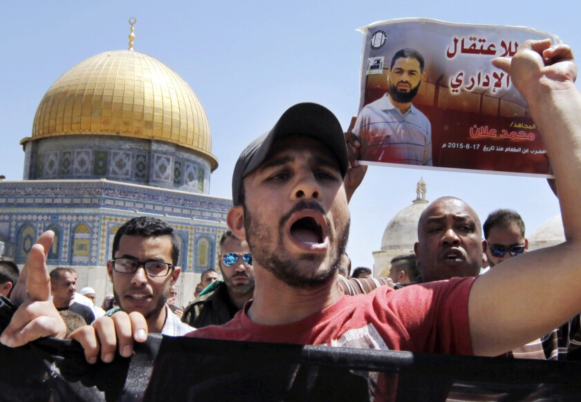 Palestinian demonstrators chant slogans and carry a poster of hunger striker Mohammed Allan during a protest in Jerusalem's Old City on Aug. 14.