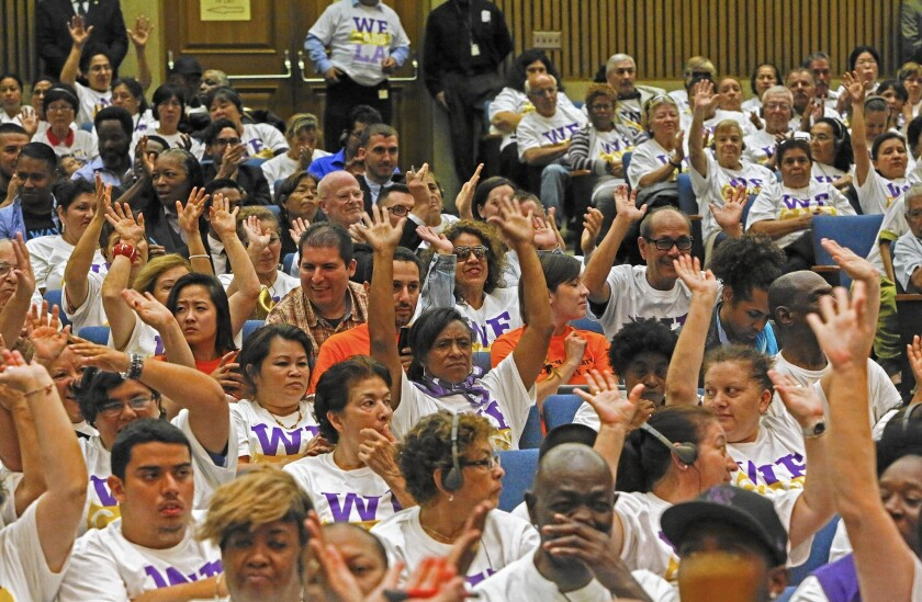People at a Los Angeles County Board of Supervisors meeting show their support for providing a drug that can prevent HIV infections.