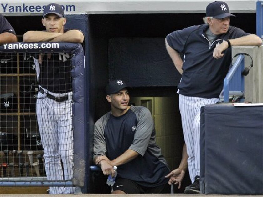 New York Yankees manager Joe Girardi (left), pitcher Andy Pettitte (center) and pitching coach Larry Rothschild watch a spring training game in 2012.