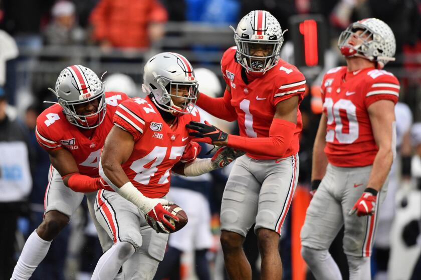 Justin Hilliard celebrates with his Ohio State teammates after intercepting a pass.