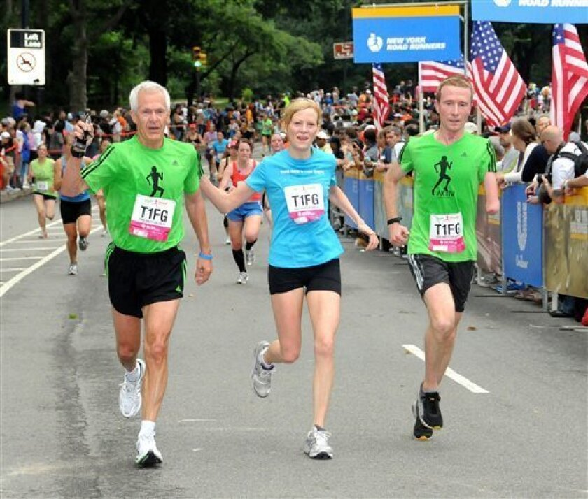 In this photo provided by the New York Road Runners, Jack Waitz, left, husband of the late Grete Waitz, joins New York Road Runners president Mary Wittenberg and an unidentified man, on the course of the New York Mini 10-kilometer race, Saturday, June 11, 2011, in New YOrk. This year's race is dedicated to marathon star Grete Waitz, who died of cancer in April. Her husband is the first male to compete in the event traditionally reserved for women. (AP Photo/New York Road Runners)