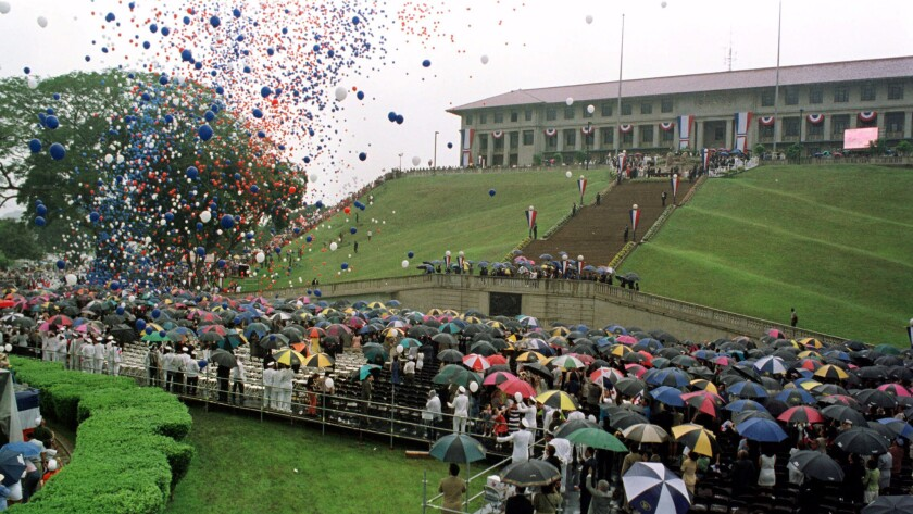 Balloons are released over a crowd huddled under umbrellas at the Panama Canal Adminstration Building during the ceremony transferring the canal to Panamanian control on Dec. 31, 1999.