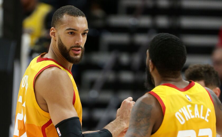 Jazz center Rudy Gobert talks to teammate Royce O'Neale (23) during a game earlier this season.