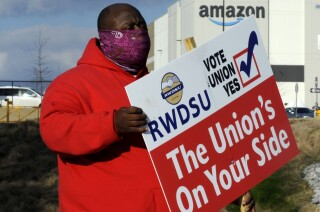 Michael Foster of the Retail, Wholesale and Department Store Union holds a sign outside an Amazon facility where labor is trying to organize workers on Tuesday, Feb. 9, 2021. President Joe Biden said workers in Alabama and across the country have the right to join a union without intimidation from their companies. His comments come as Amazon workers in the state are voting on whether they should unionize. In a two minute video posted to Twitter, Biden didn't mention Amazon by name, or say how workers should vote. (AP Photo/Jay Reeves, file)