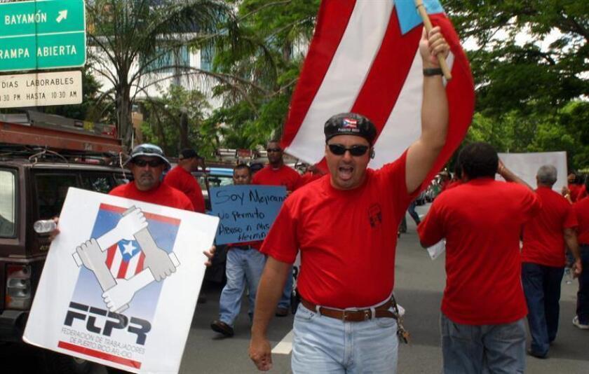 Francisco Aponte grita consignas mientras porta la bandera puertorriqueña durante una manifestación de la Unión de Trabajadores de las Comunicaciones de Puerto Rico que se realizó el miércoles 26 de abril de 2006, en la avenida Roosevelt de Hato Rey, para denunciar la venta de Verizon a Telmex. EFE/Archivo