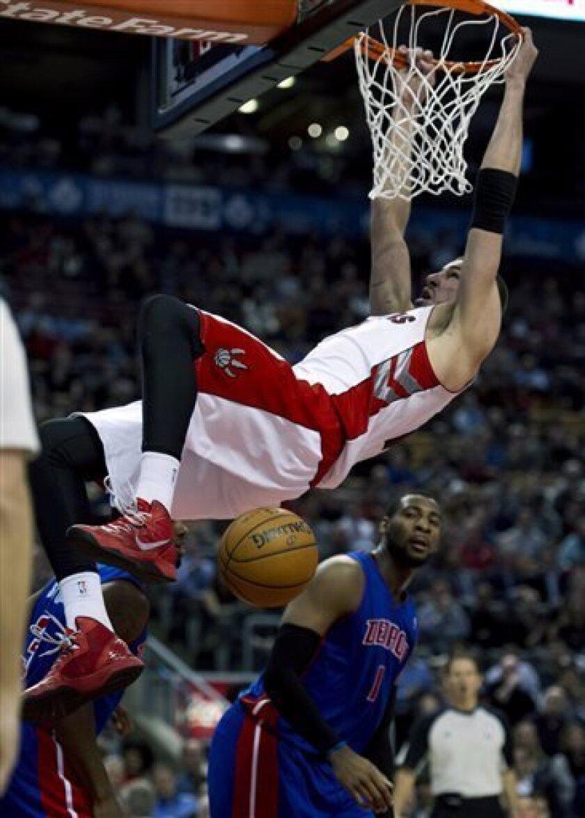 Toronto Raptors center Jonas Valanciunas slams a dunk over Detroit Pistons center Andre Drummond (1) during the first half of an NBA basketball game in Toronto on Monday, April 1, 2013. (AP Photo/The Canadian Press, Frank Gunn)