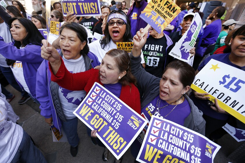 SEIU members cheer during a rally outside the Ronald Reagan State Building in downtown Los Angeles on Monday after Gov. Jerry Brown signed the state's new minimum wage bill into law.