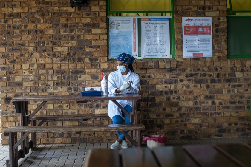 Carol Ditshego waits for patients coming for a COVID-19 test at the Ndlovu clinic in Elandsdoorn, 200 kms north-east of Johannesburg Thursday Feb. 11, 2021. The Ndlovu center is running a study of the Johnson & Johnson COVID-19 vaccine with 602 people from the community participating. (AP Photo/Jerome Delay)