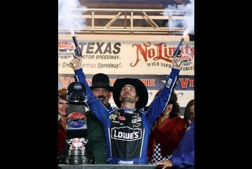FILE - In this Nov. 4, 2012, file photo, Jimmie Johnson fires blanks out of a pair of revolvers as he celebrates his win in Victory Lane following the NASCAR Sprint Cup Series auto race at Texas Motor Speedway, in Fort Worth, Texas. The National Rifle Association is taking its relationship with racing to a new level as the title sponsor of a NASCAR Sprint Cup Series race. The deal with Texas Motor Speedway comes at a time when the NRA is involved in a renewed debate on gun violence in the wake o