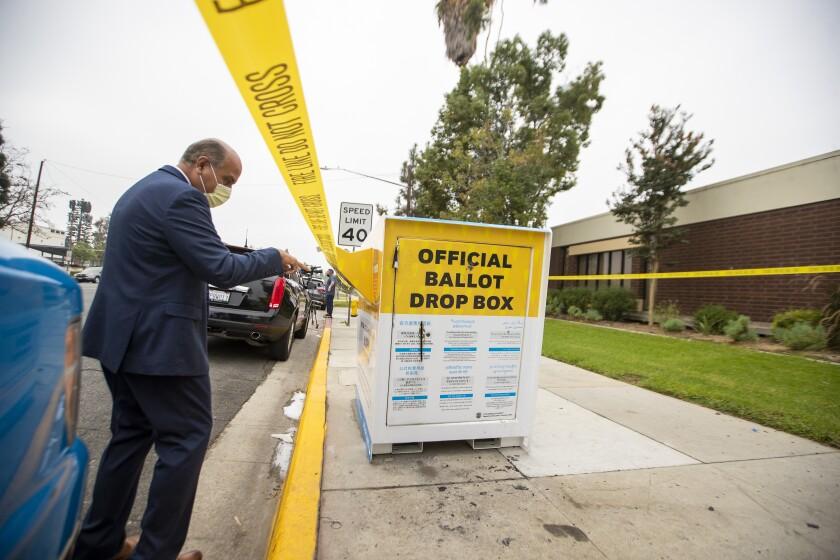 Baldwin Park Mayor Manuel Lozano views the fire damage to a ballot drop box.