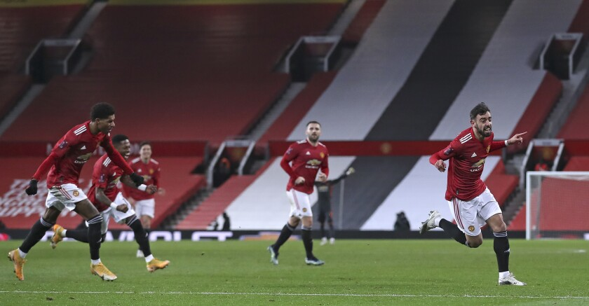 Manchester United's Bruno Fernandes, right, celebrates scoring his side's third goal during the English FA Cup 4th round soccer match between Manchester United and Liverpool at Old Trafford in Manchester, England, Sunday, Jan. 24, 2021. (Martin Rickett/Pool via AP)