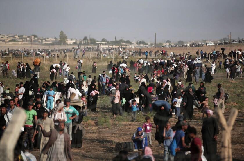 Esta fotografía de archivo tomada desde el lado turco de la frontera entre Turquía y Siria, en Akcakale, provincia de Sanliurfa, muestra a miles de refugiados sirios caminando para ingresar a Turquía. Después de un comienzo lento, es cada vez más probable que el gobierno del presidente Barack Obama alcance el objetivo de admitir en Estados Unidos 10.000 refugiados sirios antes del final de septiembre de 2016. (AP Foto/Lefteris Pitarakis, archivo)