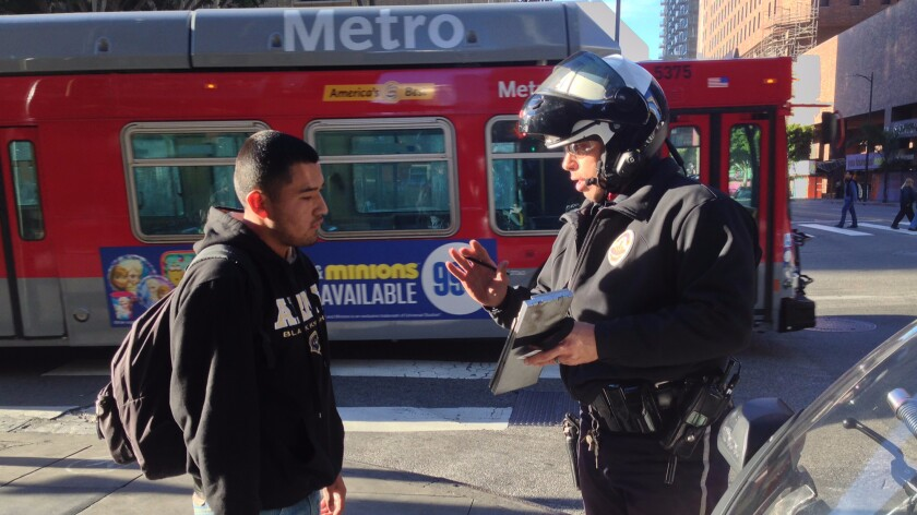 Eduardo Lopez receives a citation from LAPD motor officer Robert Lockhart in January 2015 for stepping into the intersection at Hope and 7th Street  downtown after the red flashing hand and countdown timer has begun.