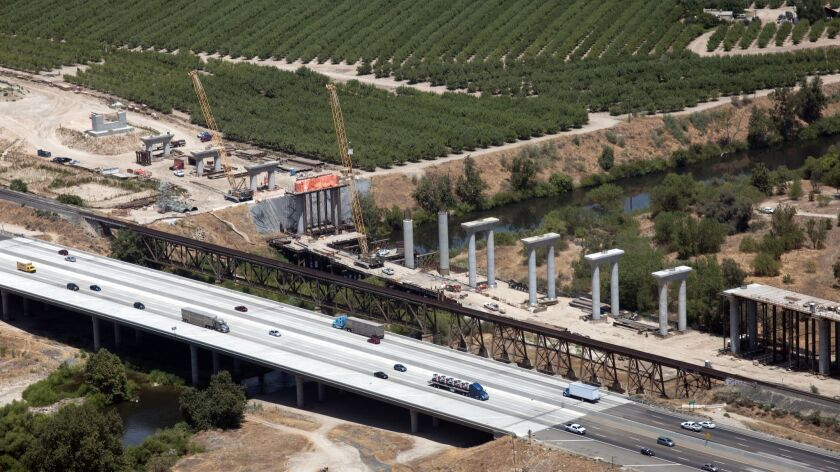 At the San Joaquin River Viaduct, workers continue pouring concrete for the pergola deck that will c