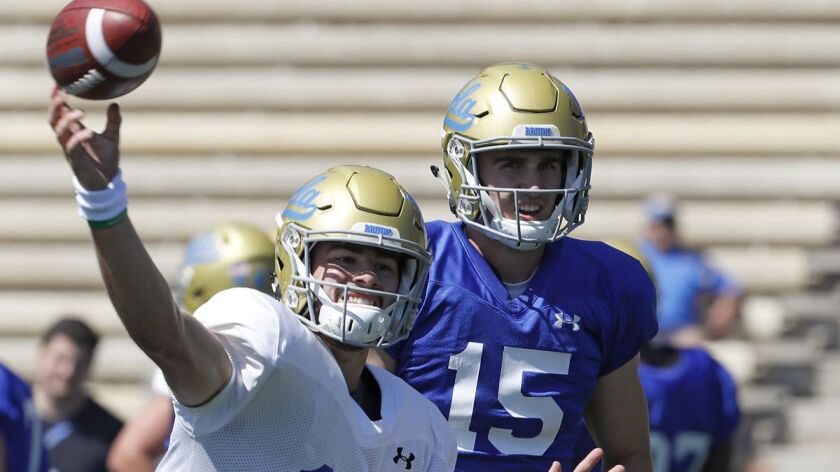 LOS ANGELES, CALIF. - APR. 21, 2018. UCLA quarterbacks Jackson Gibbs (17) and Matt Lynch (15) warm