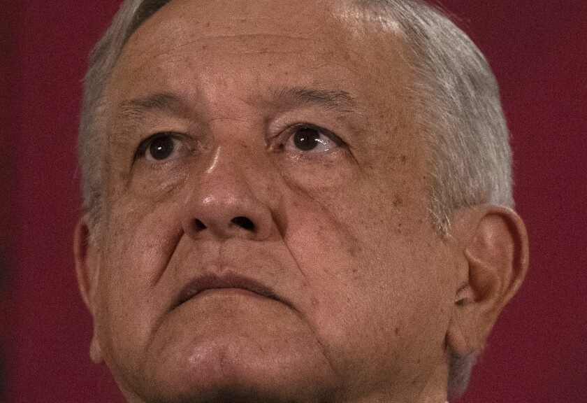 Mexico's President Andres Manuel Lopez Obrador looks up during his daily, morning news conference at the presidential palace, Palacio Nacional, in Mexico City, Monday, July 13, 2020. (AP Photo/Marco Ugarte)