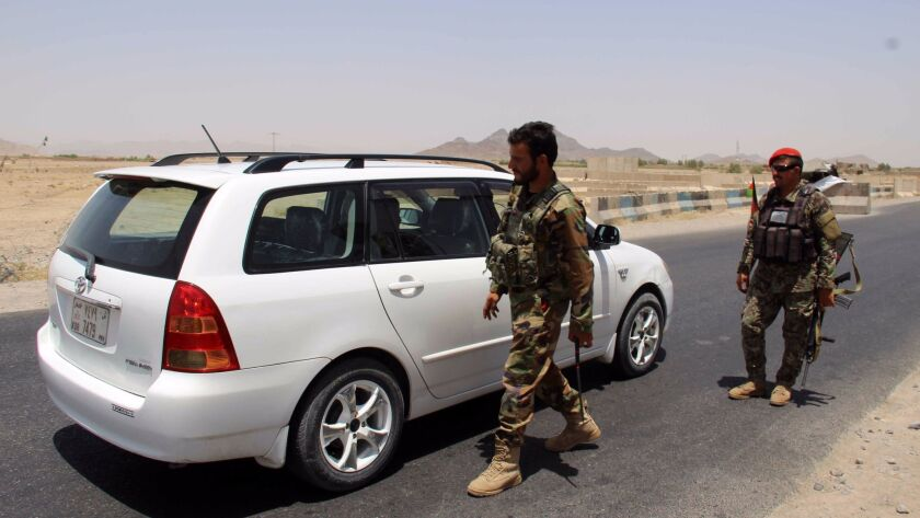 Afghan soldiers search vehicles Thursday at a checkpoint on a highway leading to the Maiwand district of Kandahar.